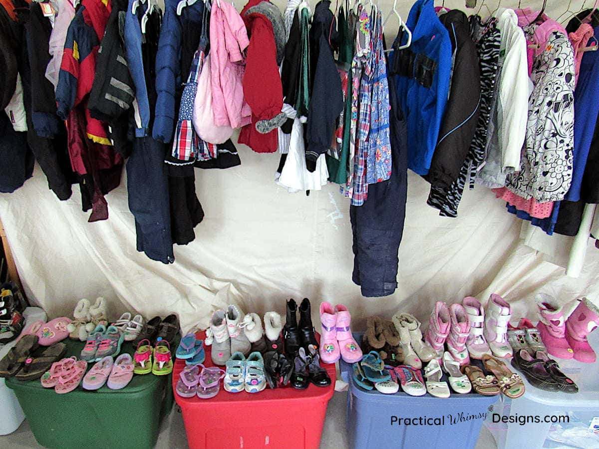 Hanging clothes and shoes for sale at a garage sale