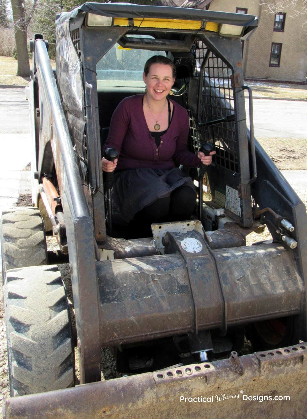 Lady sitting in a bobcat smiling