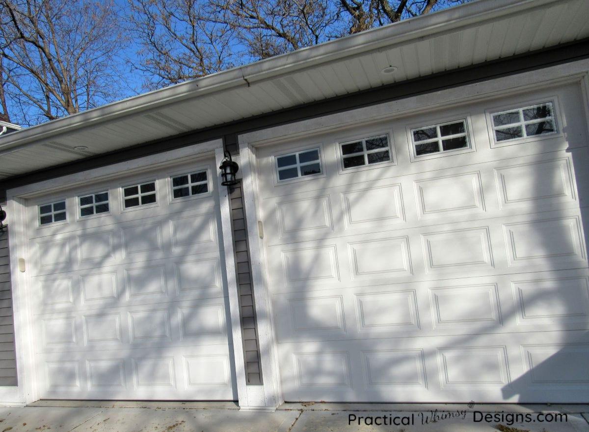 White garage doors and grey siding on garage