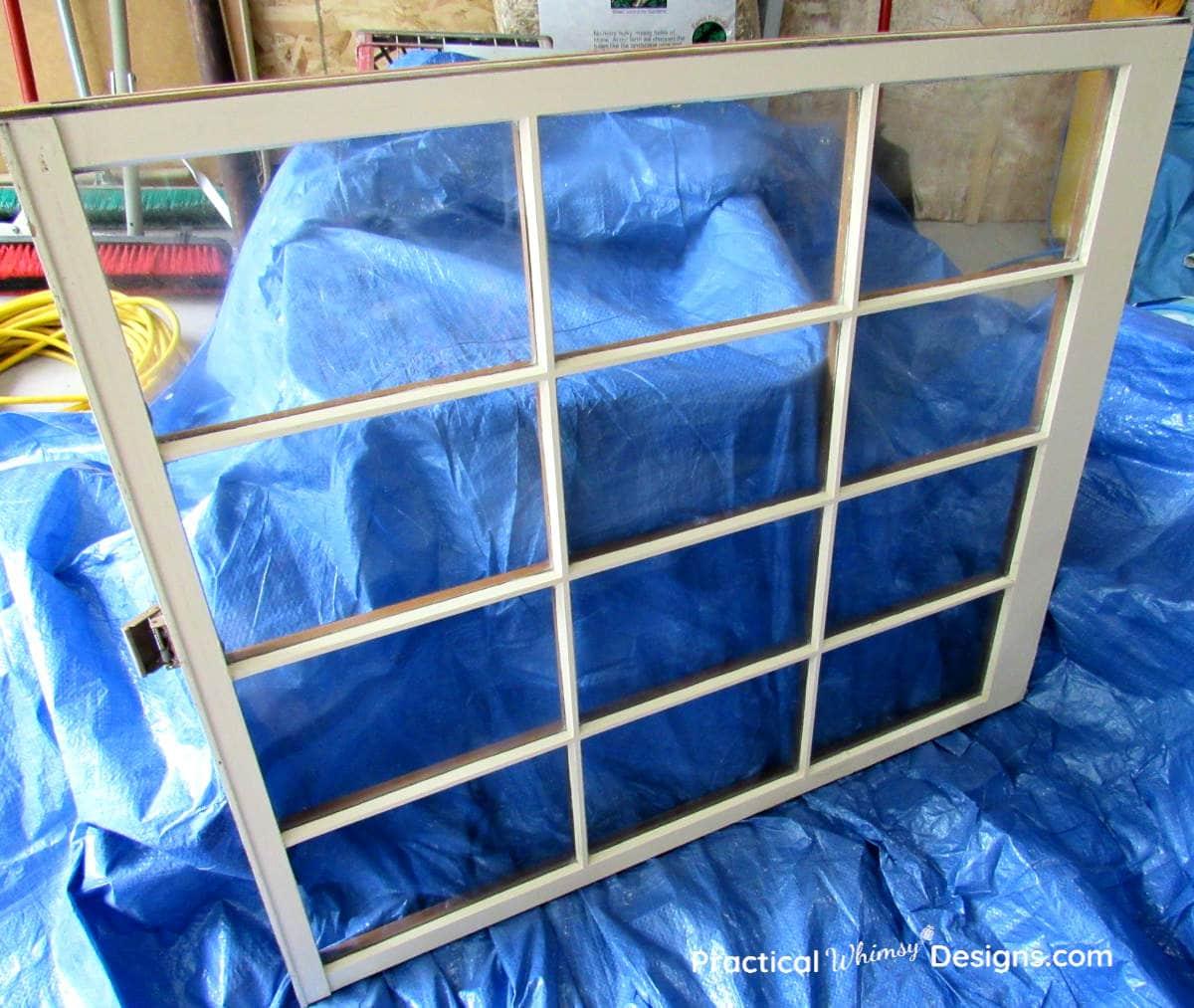 Glass window leaning against blue tarp
