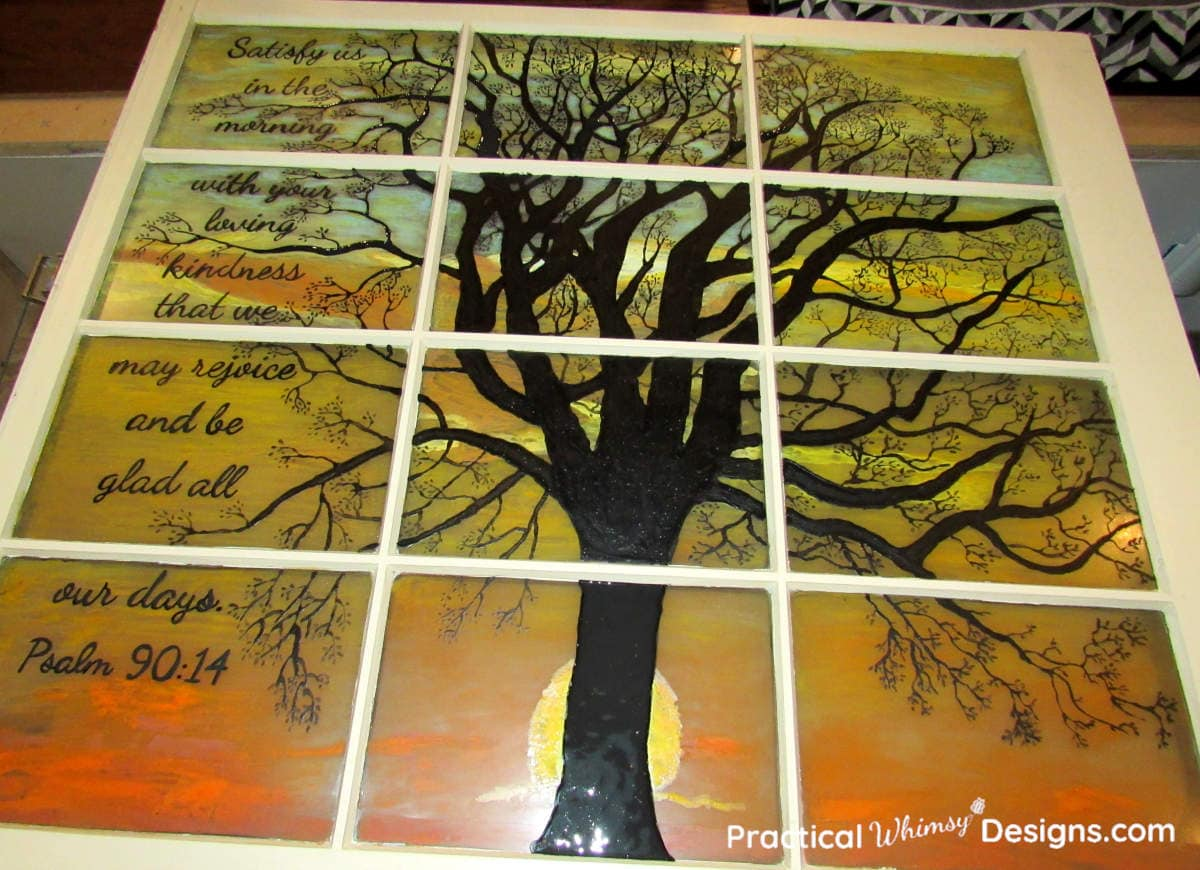 Black tree silhouette and verse on glass window