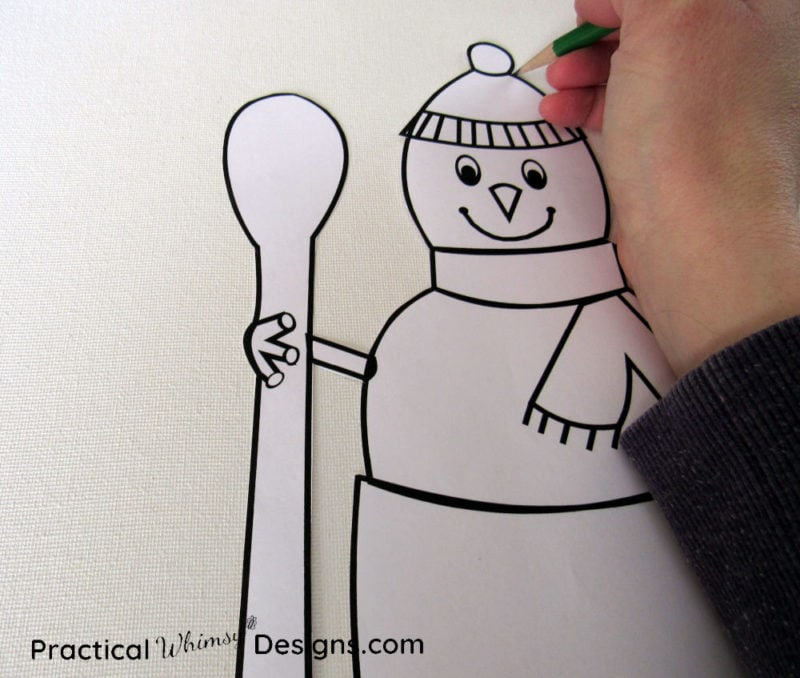 Tracing snowman on canvas with a pencil