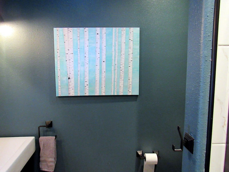 Birch tree painting hanging on blue wall