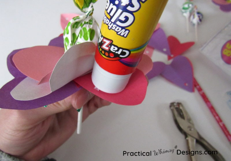 Gluing hearts on valentines card flowers