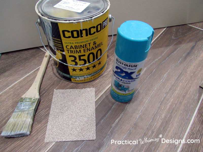 Paint, brush, and sandpaper for distress painted furniture