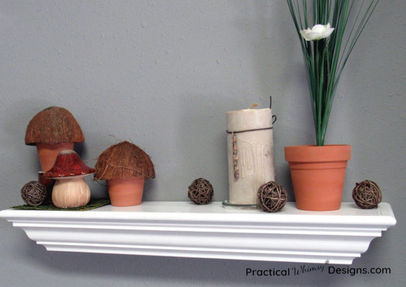 DIY mushroom decor on shelf with candle and flower