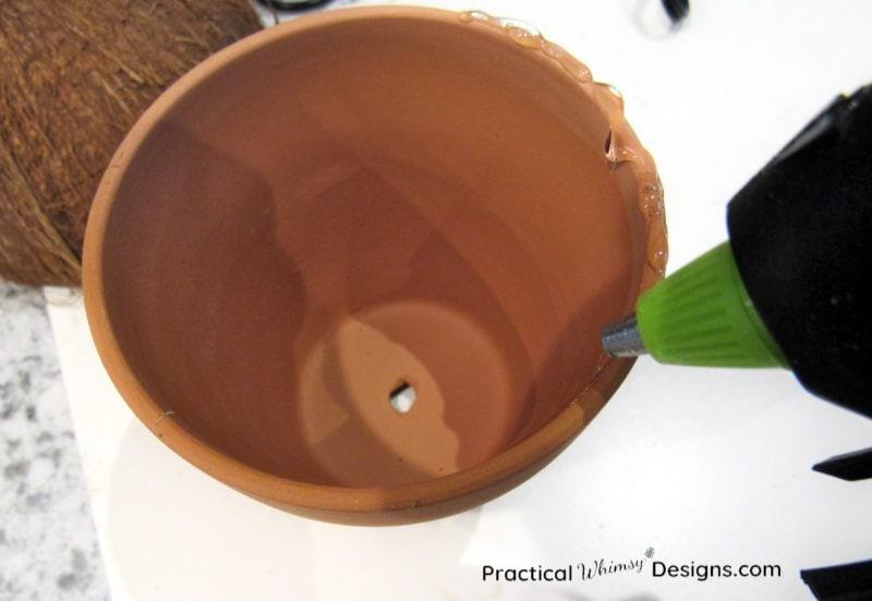 Hot gluing rim of clay pot