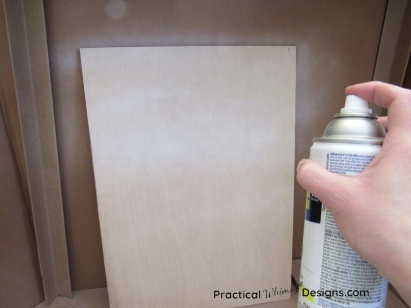 Spraying primer on a piece of plywood