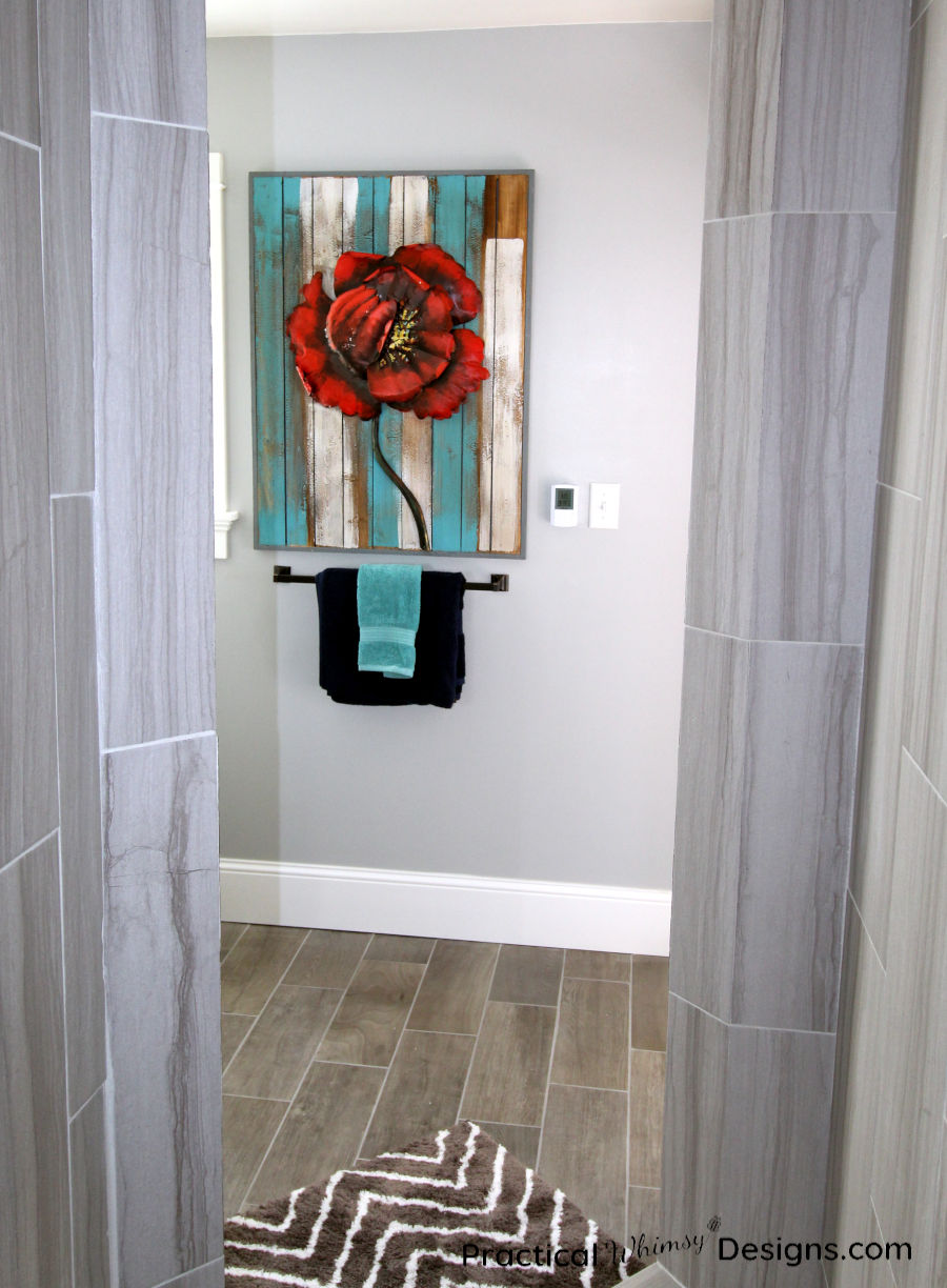 Red Flower picture hanging above blue towels