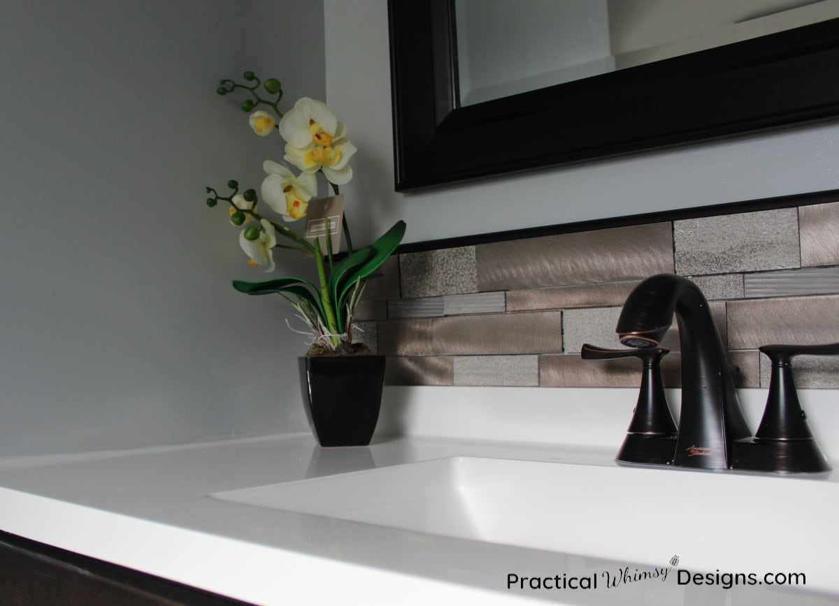 Sink and faucet with white orchid sitting on it