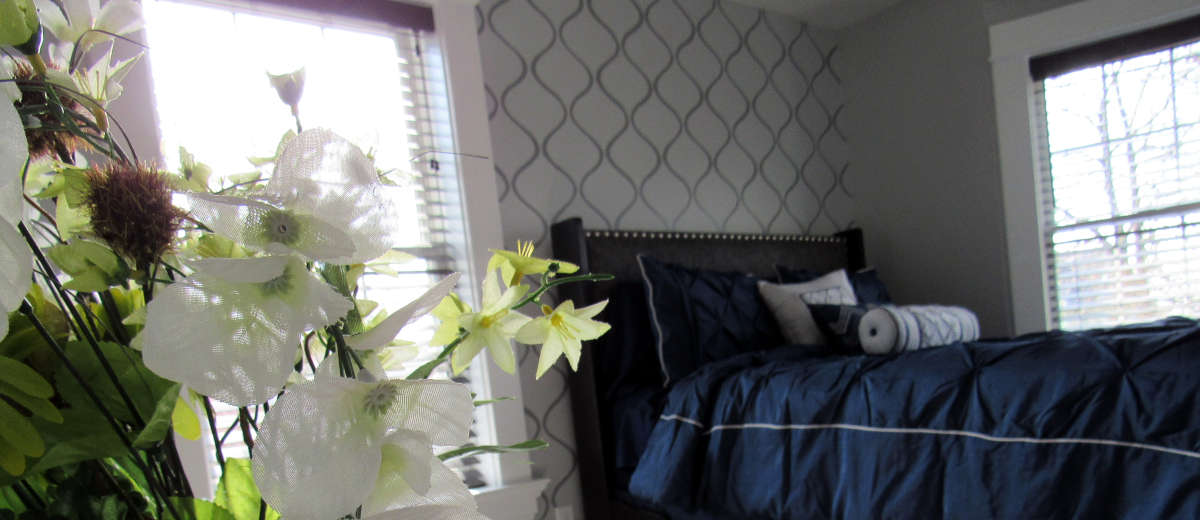 Bedroom with flowers and wall stencil