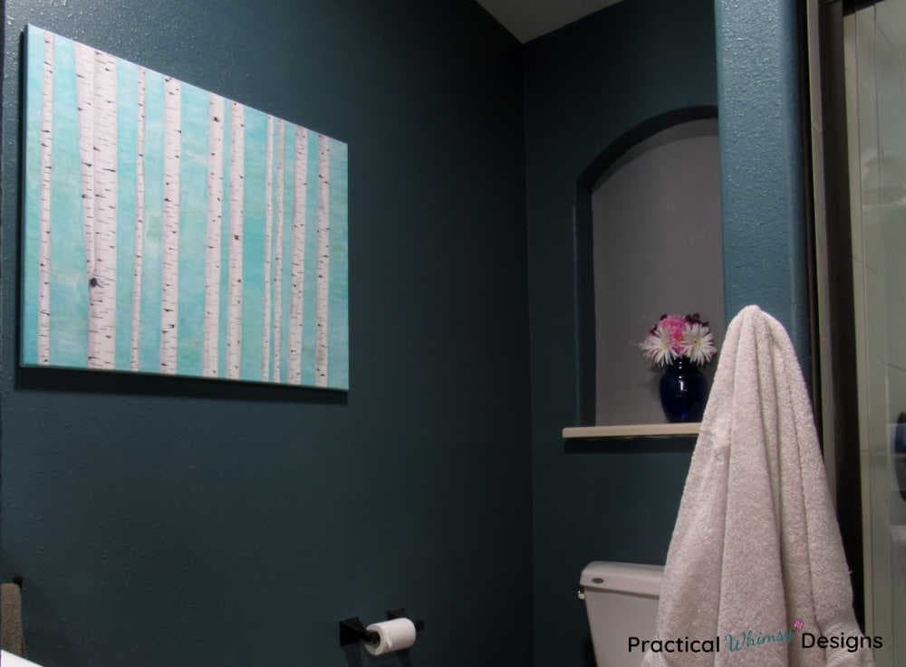 Birch tree painting hanging in bathroom with flowers on shelf.