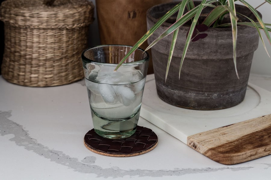 Woven leather coaster on table with glass of ice water