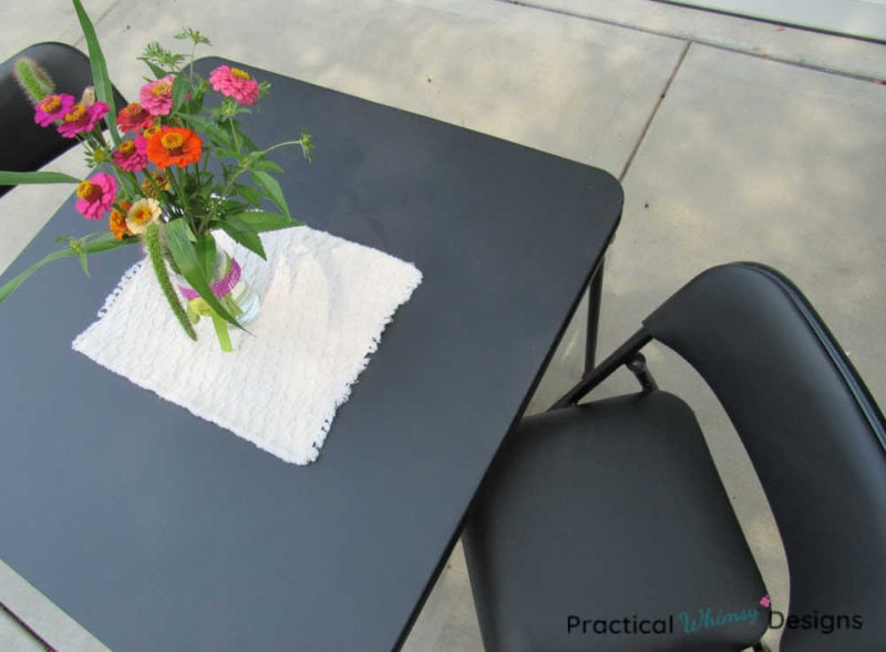 Refinished card table and chair with flowers on it.