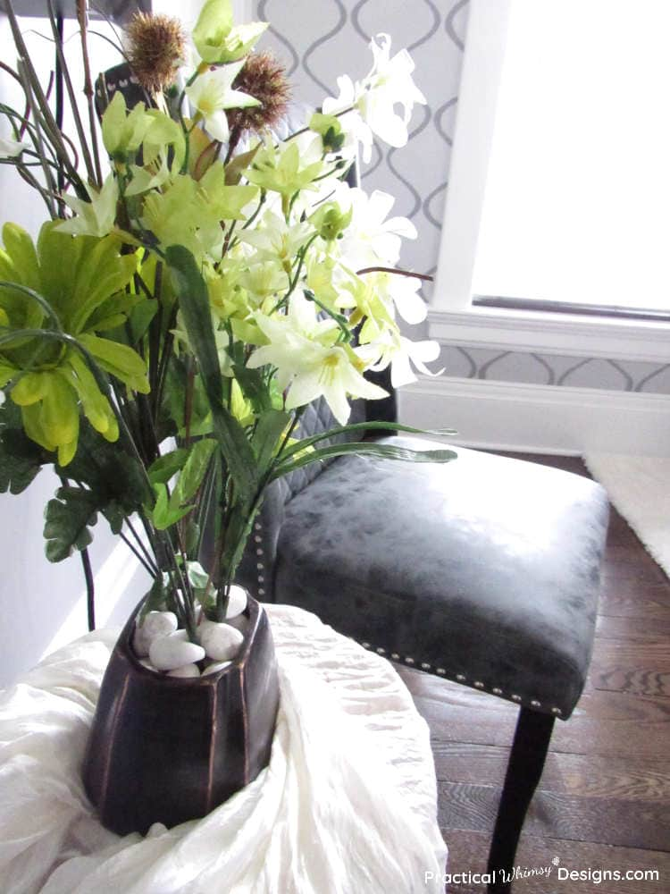 Bronze vase with green and white flowers