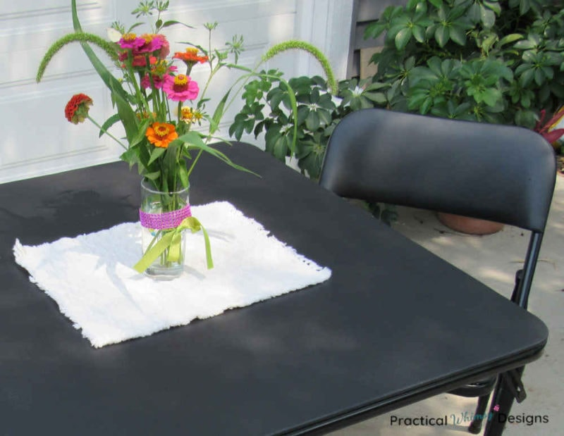 Butterfly on flowers sitting on refinished folding table