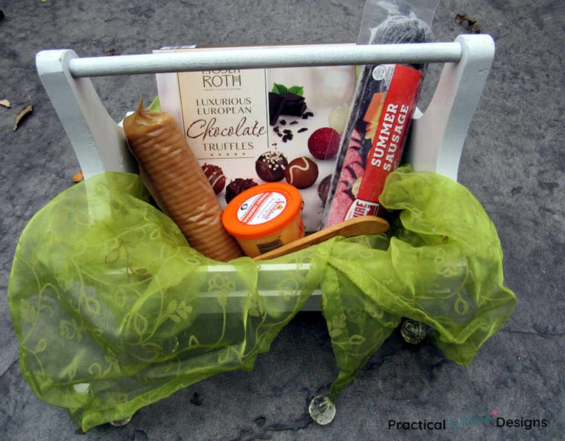 Chocolate, cheese, sausage, and crackers in a wooden caddy with a green cloth draped on the side