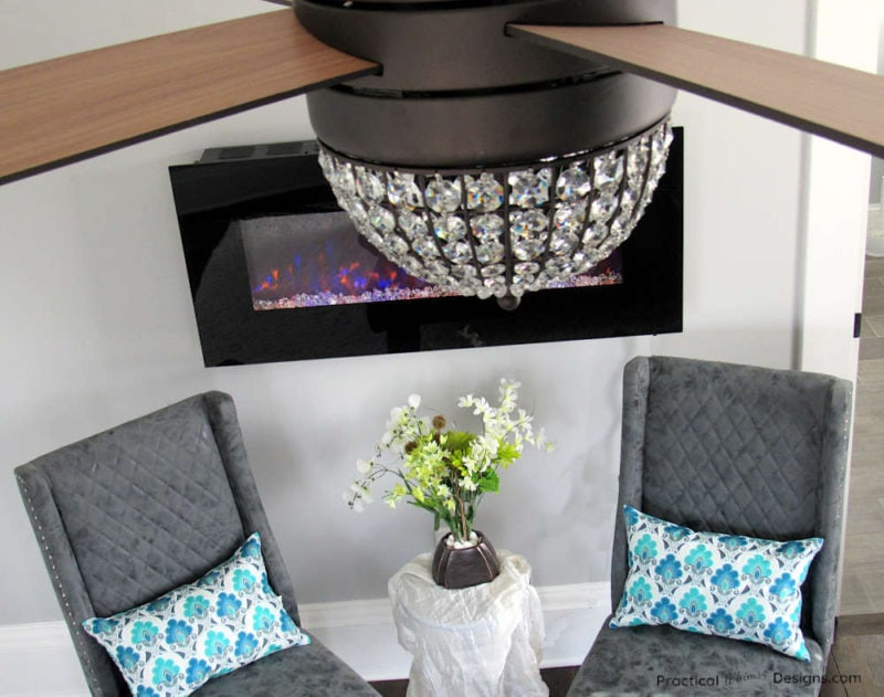 Grey chairs underneath electric fireplace with small table and flowers