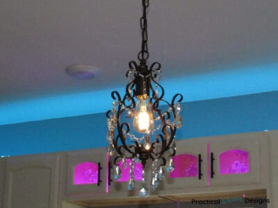 Glass chandelier hanging in front of cabinets with blue and pink lighting