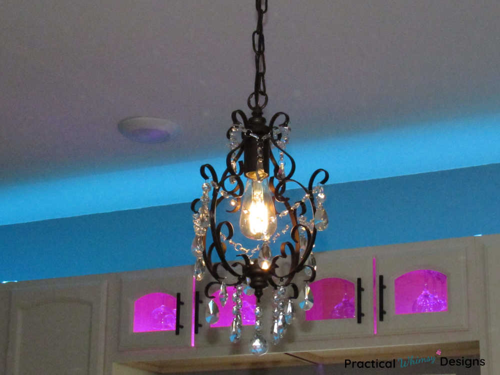 Glass chandelier in front of cabinets with pink and blue lighting
