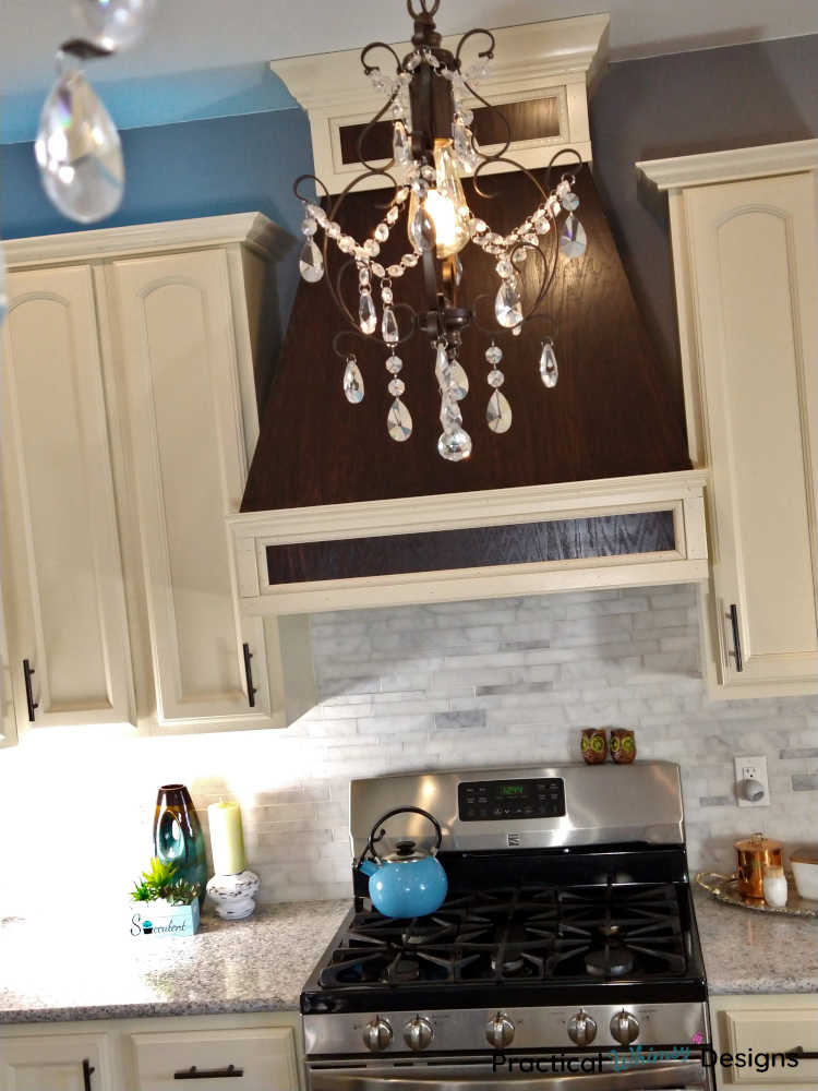 Glass chandelier hanging in front of custom wooden stove vent in remodeled kitchen