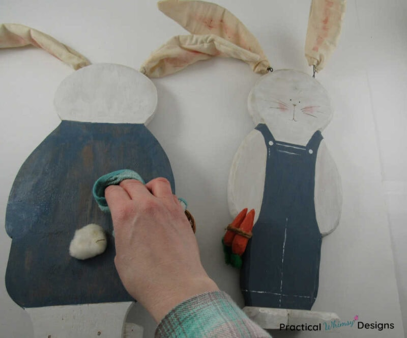 Cleaning painted wooden bunny decor with rag