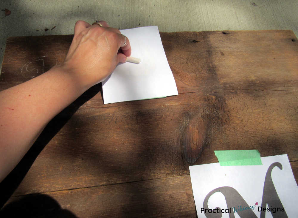 Coloring the back of the paper with chalk to transfer the lettering onto a wooden board.
