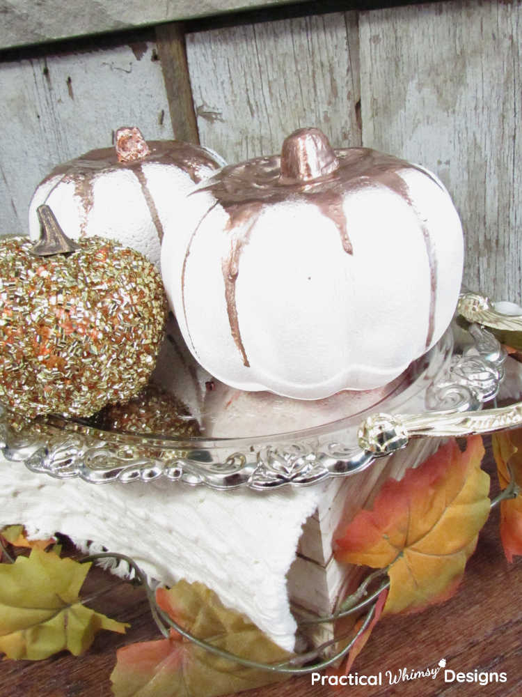 Copper dripped pumpkins and gold pumpkin on tray in front of rustic hearth wood.