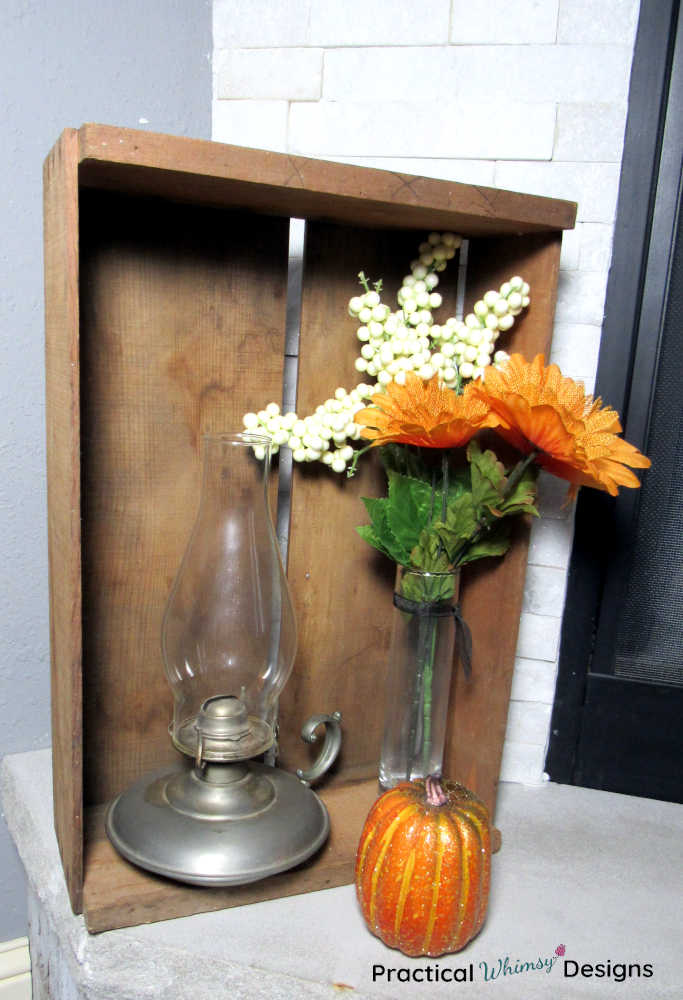 Crate, lamp, pumpkin, and fall flowers on hearth.