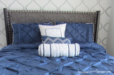 Bed with navy blue comforter, pillows, and fabric headboard