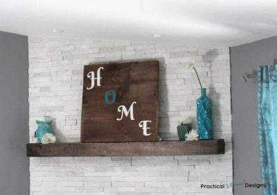 Wooden Home Sign on mantel with teal vases and white flowers