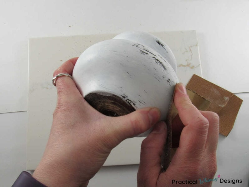 Sanding paint off of the wooden candlestick to distress it.