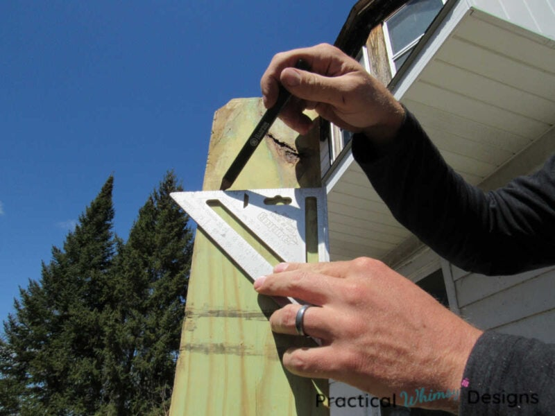 Drawing cutting line on pergola post with pencil and measuring square.