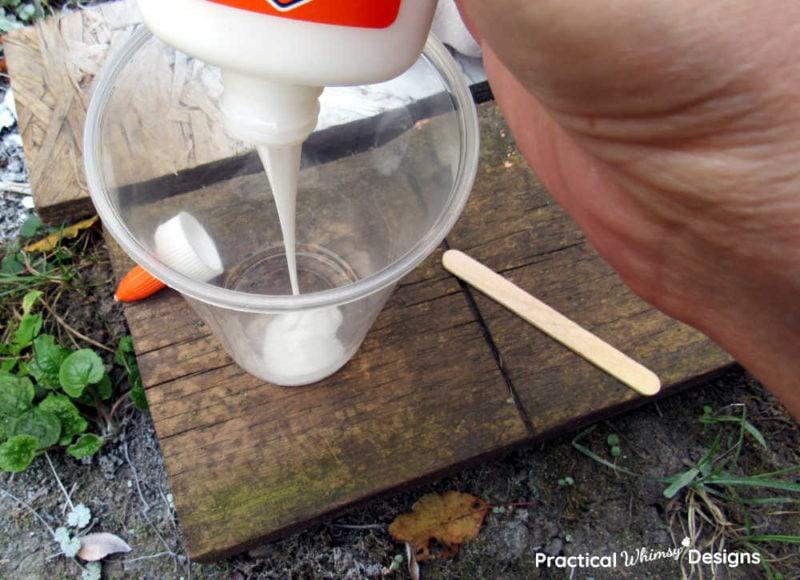 Dumping school glue in plastic cup.