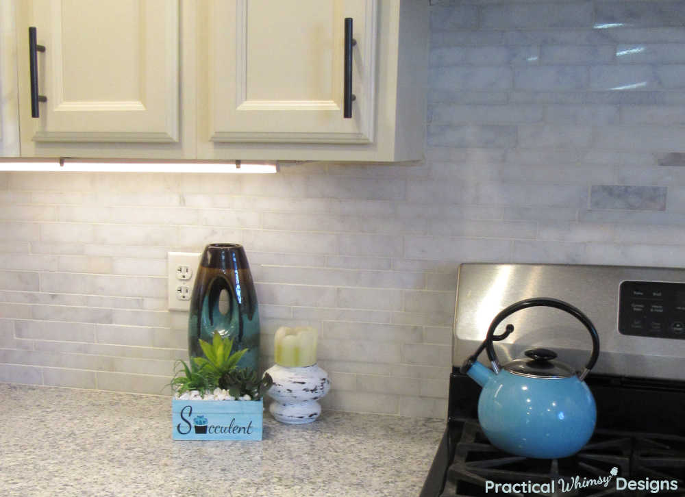 Farmhouse decorations and blue teapot in kitchen.