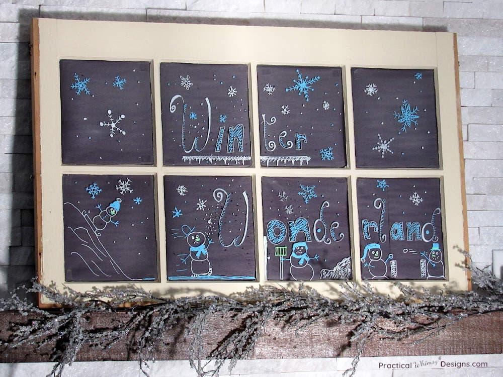 Window with winter themed chalk marker art on mantel.