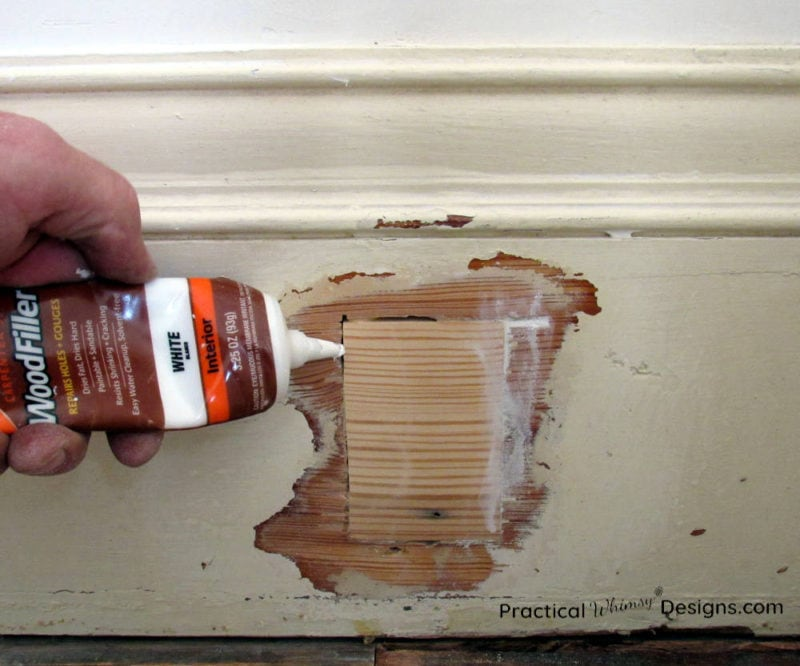 Filling gaps around trim patch with wood filler.