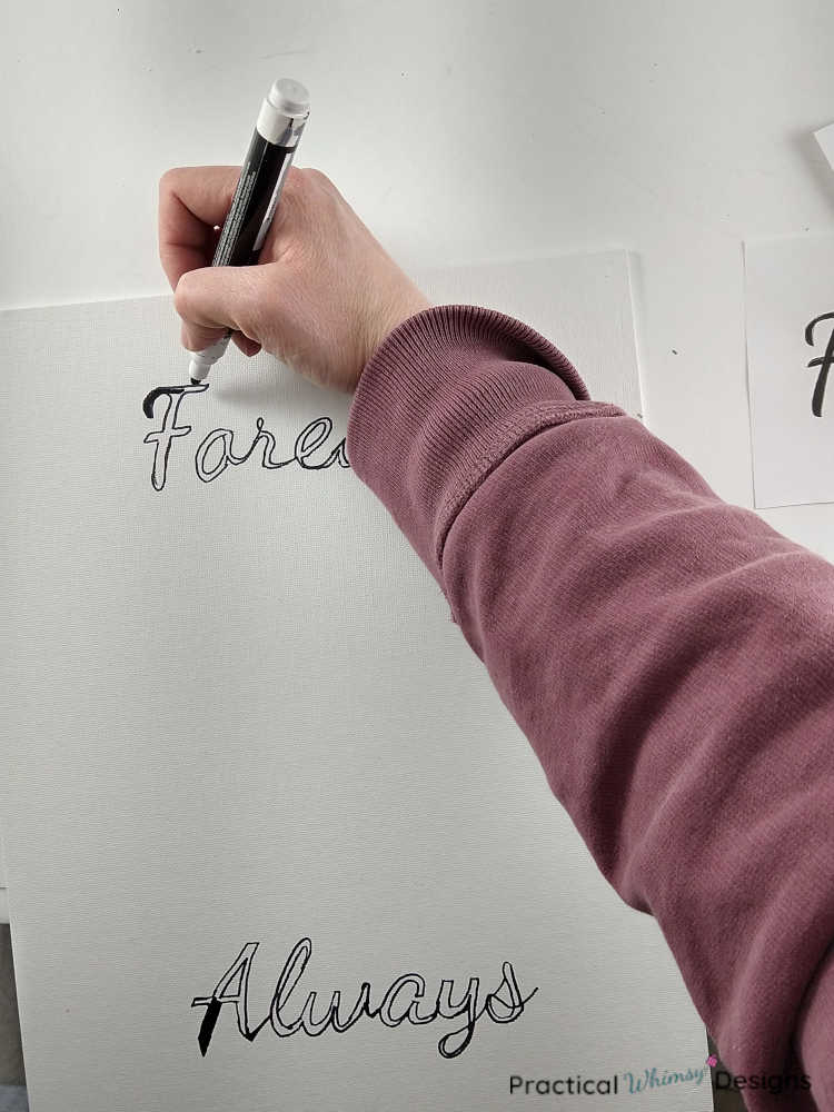 Painting words on canvas with a black acrylic paint marker.