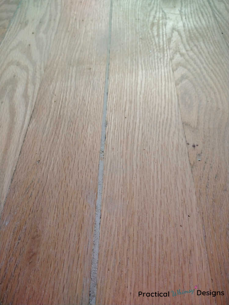 Floor with wood putty in cracks, sanded and ready for stain.