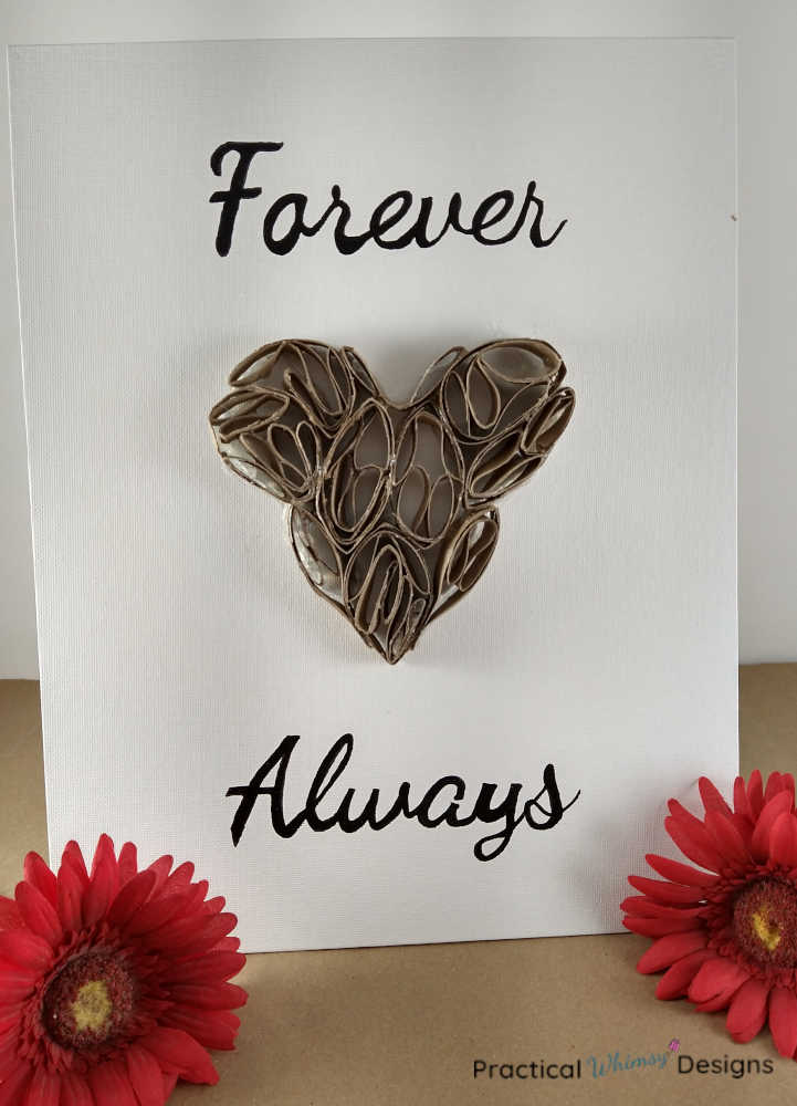 Forever Always 3D heart art on canvas with red flowers next to it.