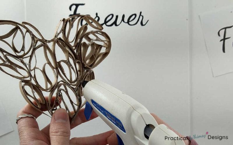 Gluing 3D paper heart onto canvas with hot glue gun.