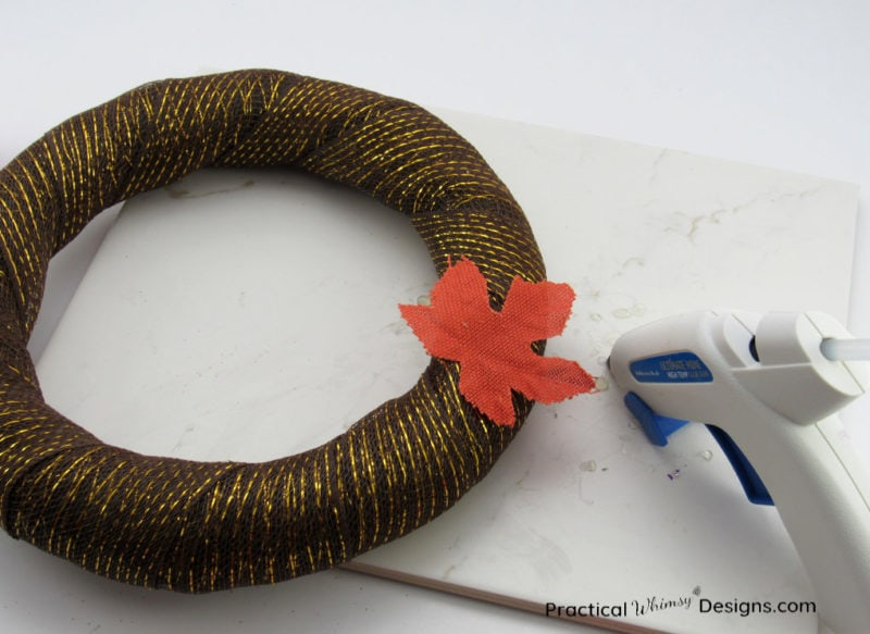 Gluing leaf on wreath.