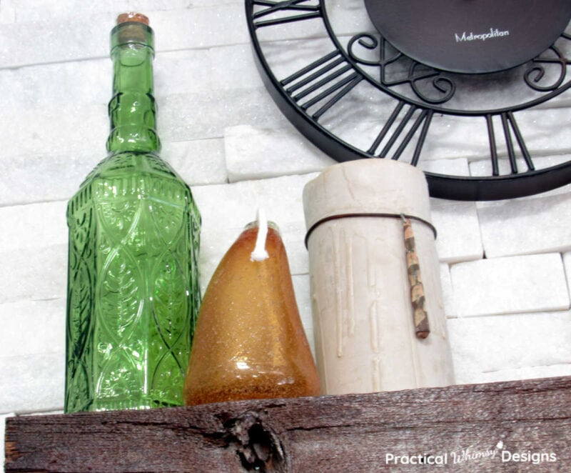 Green vase, orange lantern, and candle as part of a neutral fall decor idea for the home