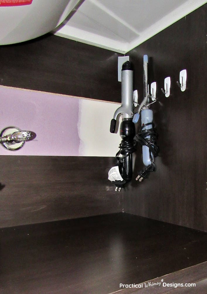 Curling irons hanging on the side of the cabinet as a small bathroom organization hack