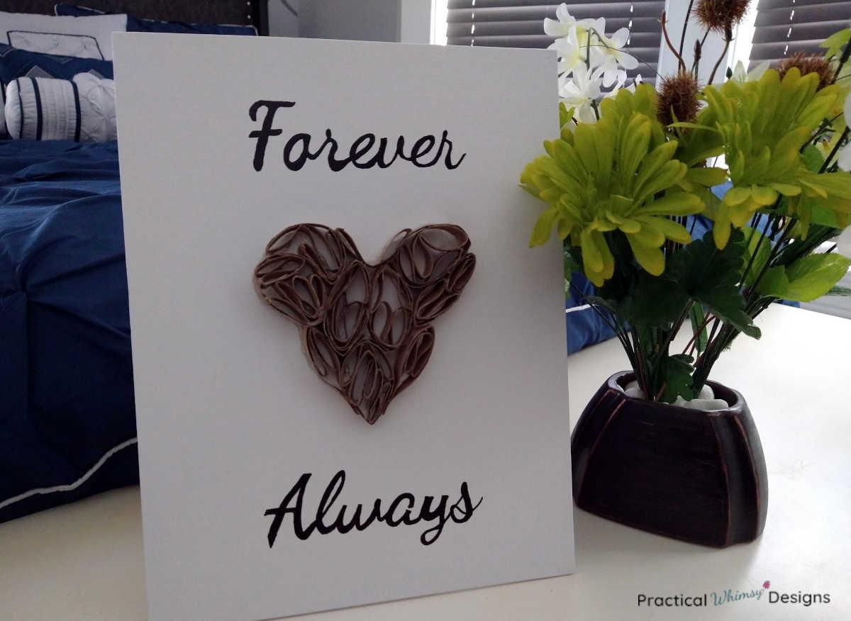 Heart toilet paper roll art on dresser next to green flowers in vase