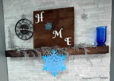 Home sign and snowflakes as part of winter mantel decor