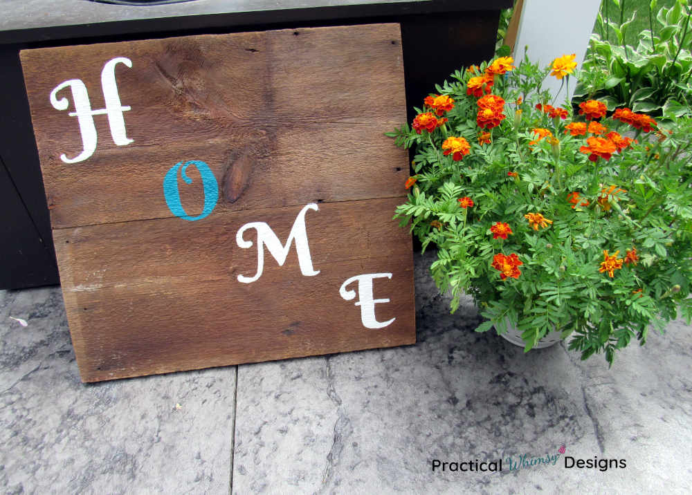 Wooden home sign next too marigold flowers