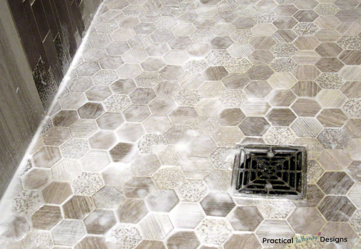 How to clean shower grout: picture of tile floor with cleaner on it.