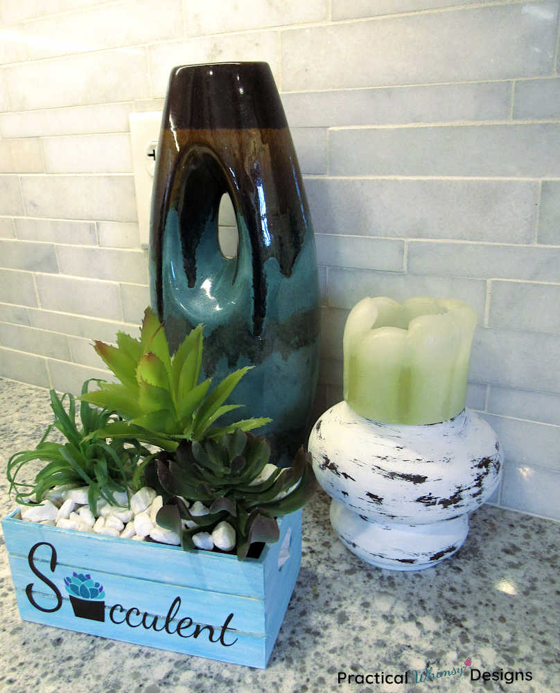 Succulent planter, farmhouse candlestick, and vase on kitchen counter.