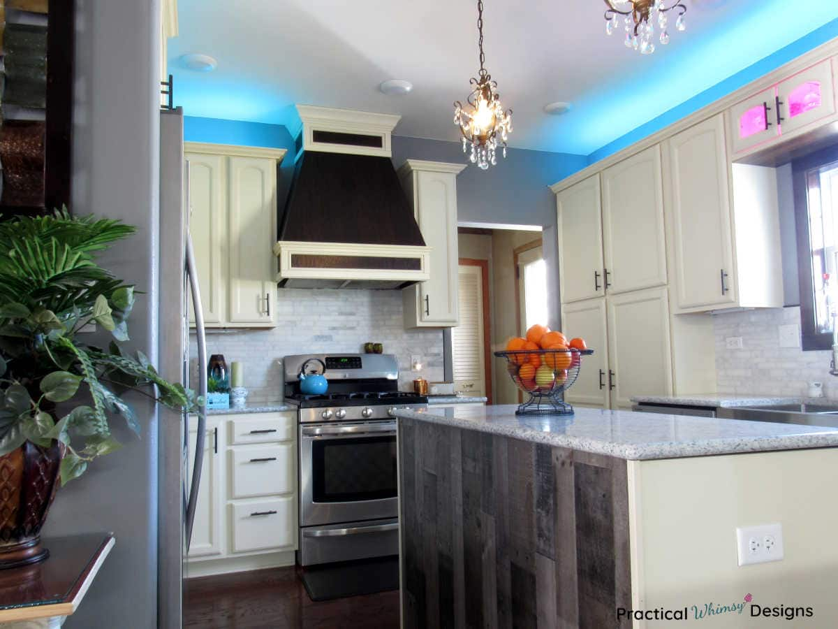 Kitchen Reveal with white cabinets, cabinet lighting, and custom stove hood vent